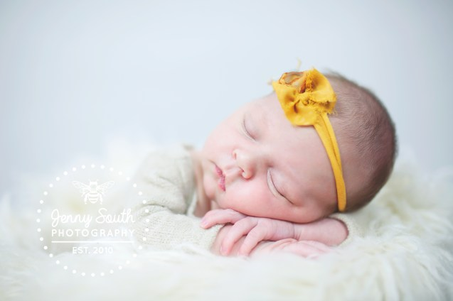 Sleeping newborn baby girl on top of soft fur against a grey background