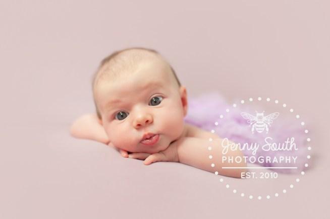 Newborn baby girl looks wide eyed with wonder during her newborn session