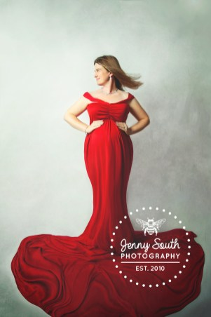 Mum to be looks stunning in a red maternity dress during a photography session