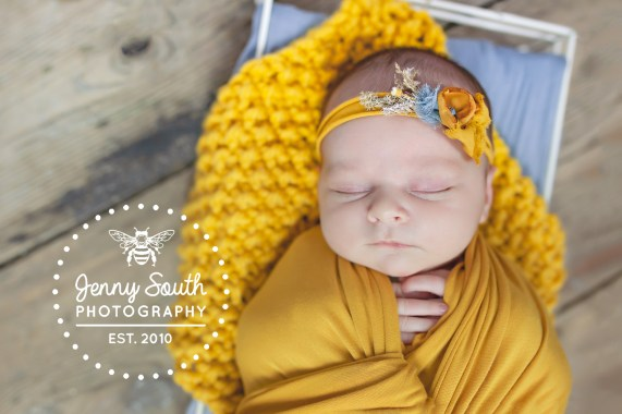 An image of a newborn baby wrapped in a mustard yellow wrap and matching headband against the grade two listed floorboards of our royal William yard newborn studio.