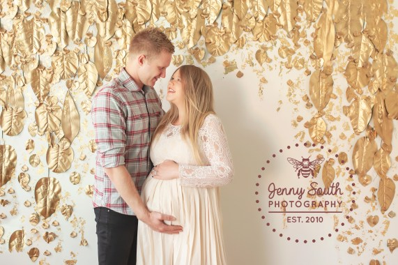 A husband and wife gaze into each others eyes as they cradle their growing bump.