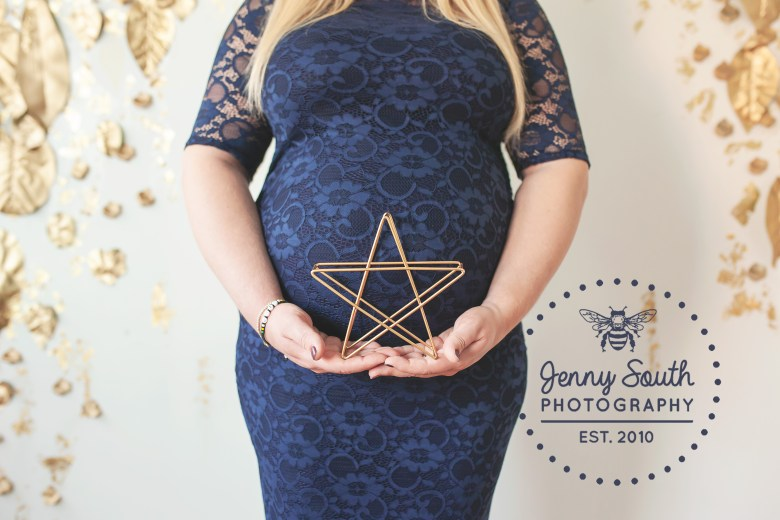 A mum holds a gold star in front of her growing baby bump.