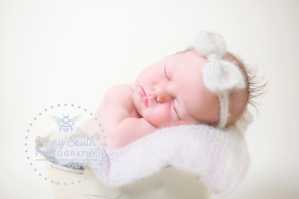 Baby girl sleeps on her hands in a metal bucket wearing a mohair wooden bow.