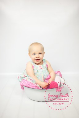 A toddler sits in a vintage enamel bowl during her first ever photo shoot