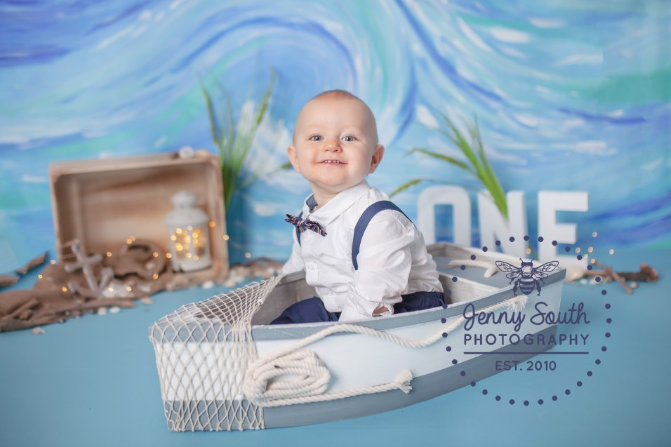 A handsom baby sits smartly dressed in a rustic wooden boat against a waterscape handprinted backdrop.