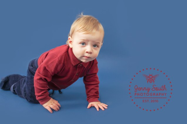 A baby boy crawls across a navy backdrop during a milestone session.