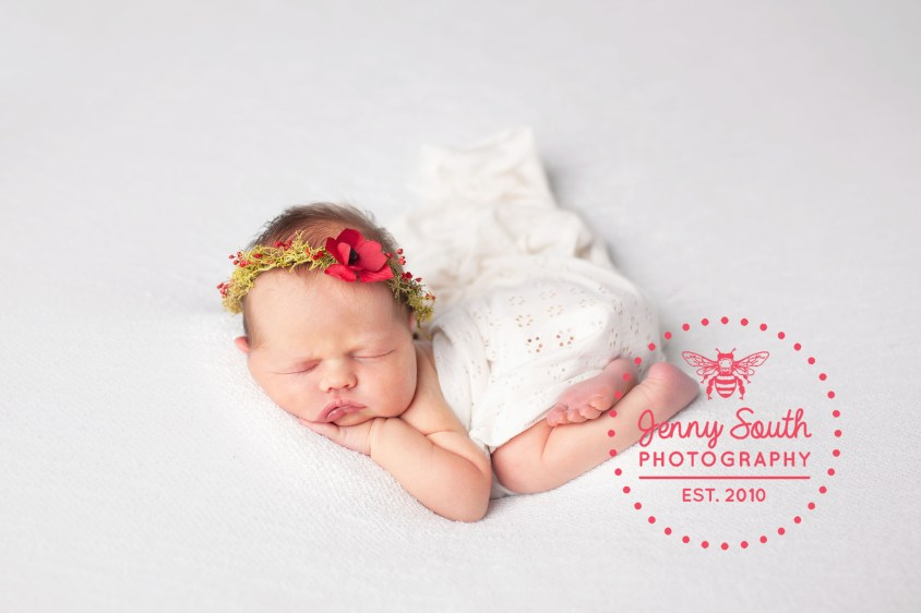 A baby girl sleeps on her belly against a white backdrop. She wears a floral tie back with a poppy on in honour of being born on remembrance day 2018