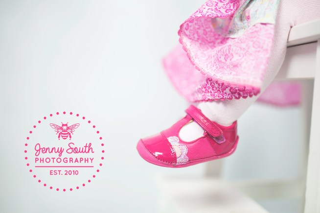 A baby wears her first pair of pink shoes