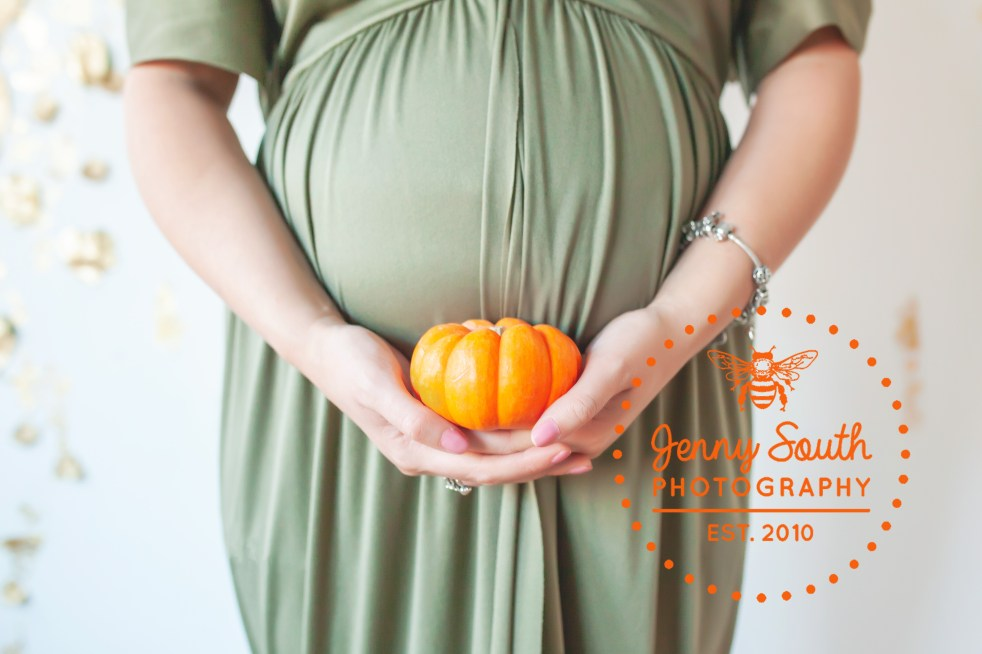 A mother holds a tiny pumpkin in front of her growing bump.