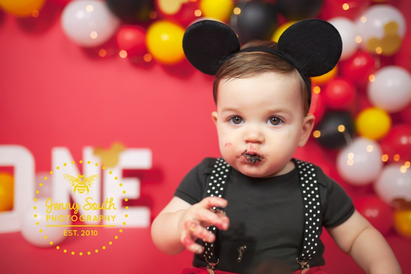 A very cute picture of a little boy with a mouth full of cake during his birthday photo shoot