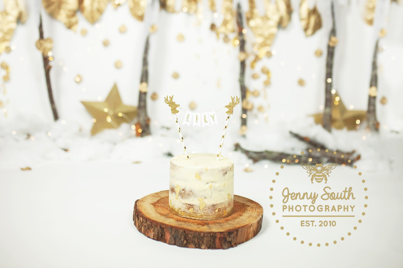 A naked cake with gold leaf details sits on top of a tree log cake stand. The cake topper is gold and white and completes the look of this Christmas cake smash