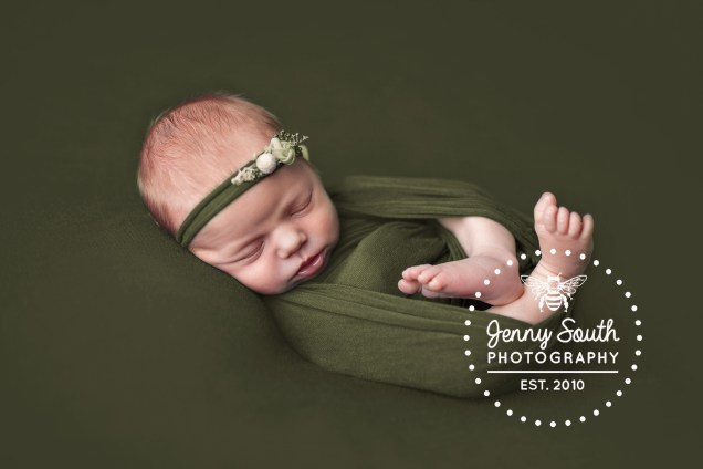 A sweet baby girl lies on an earthy green back drop wrapped in a matching wrap and headband of the same colours