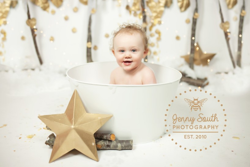 A baby girl smiles happily in a tin batch tub after a festive Christmas cake smash