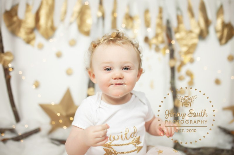 A Little Christmas baby celebrates her fist birthday with a beautiful festive session of golds and whites