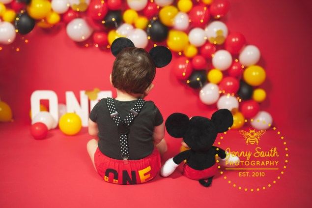 A little boy sits with his back to the camera next to his Mickey Mouse teddy showing off his Micky mouse costume.