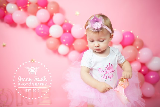 A baby girl wear a pink fabric crown and matching tutu on a custom designed set including a pink balloon wall her a photo shoot for her birthday