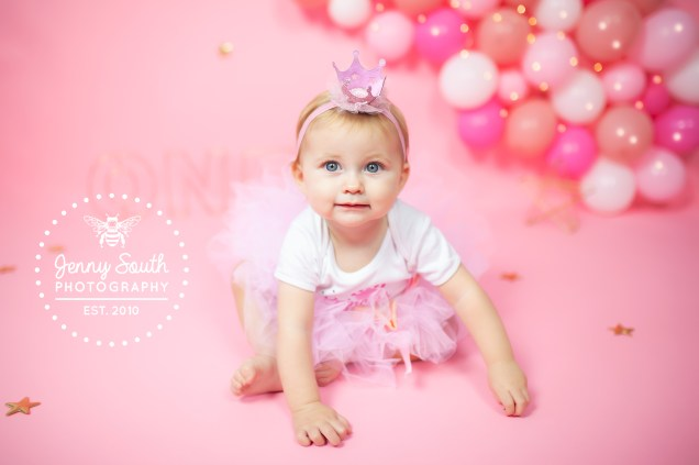 A little princess smiles sweetly in a photo for her first birhtday