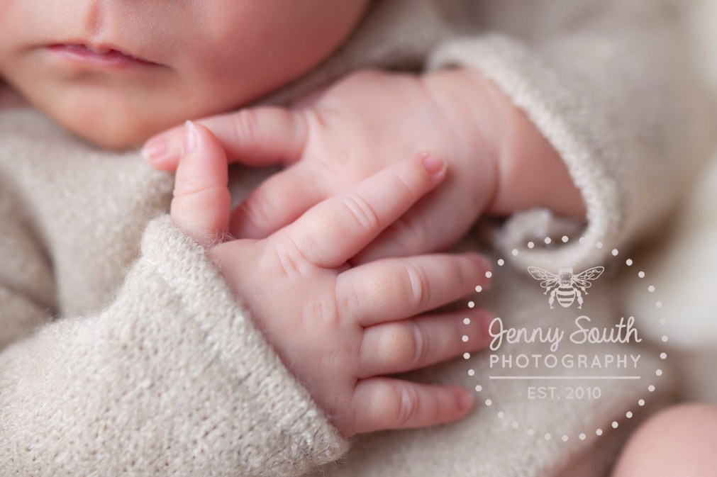 A babies delicate finger cross effortlessly as she sleeps peaceful fully during a newborn photo session