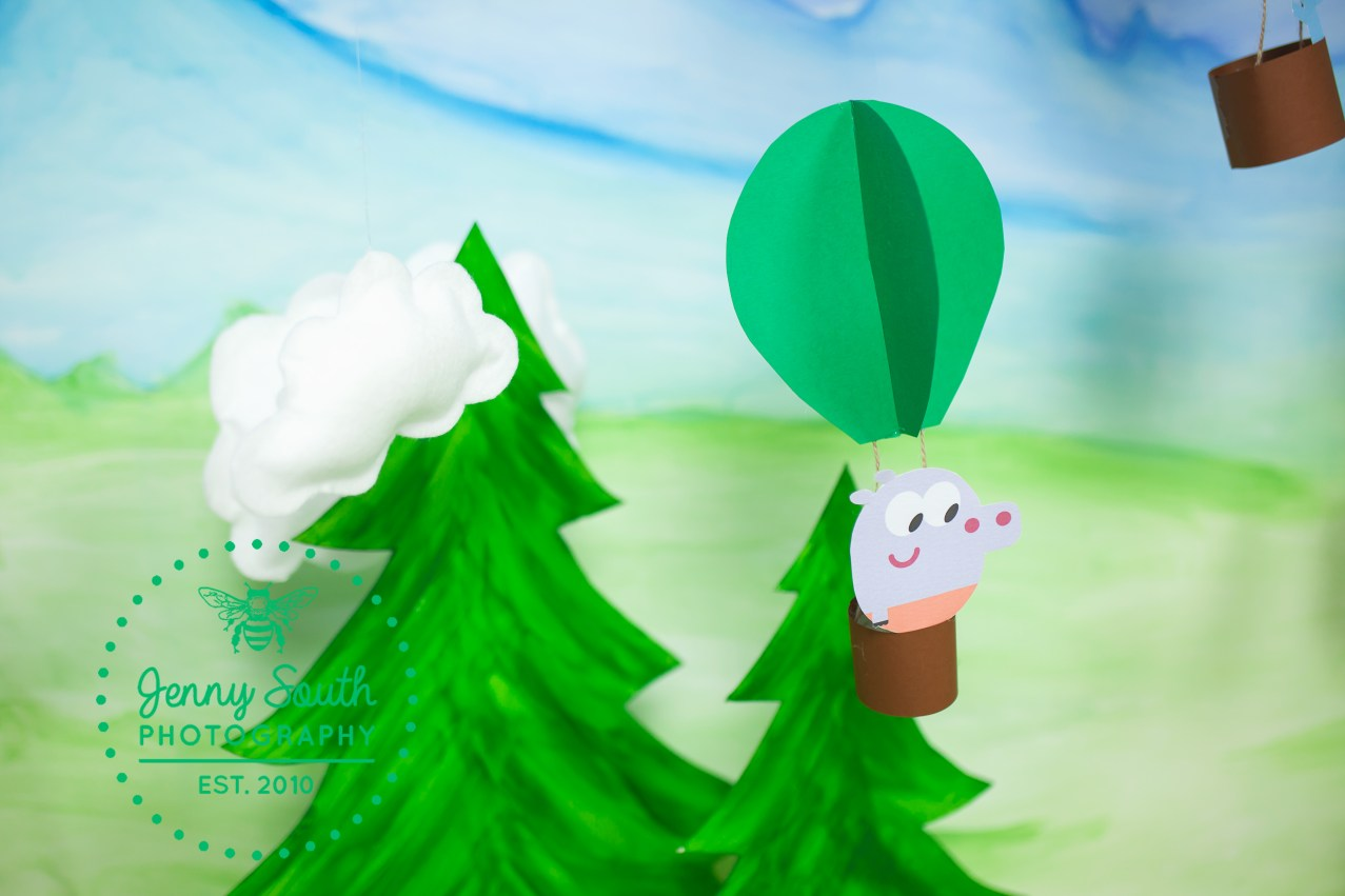 A hey Duggee squirrel flying in a hot air balloon against tree tops and mountains