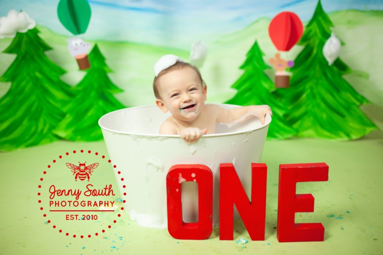 A little boy splashed in a tin bath tub against our new adventure awaits hand painted backdrop
