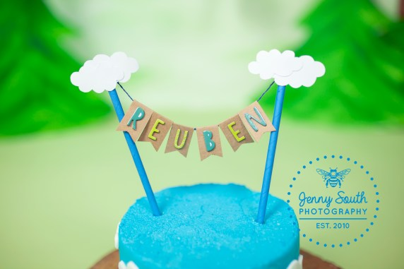 A blue birthday cake with a hand made bespoke cake topper on top spelling the name reuben with clouds attached.