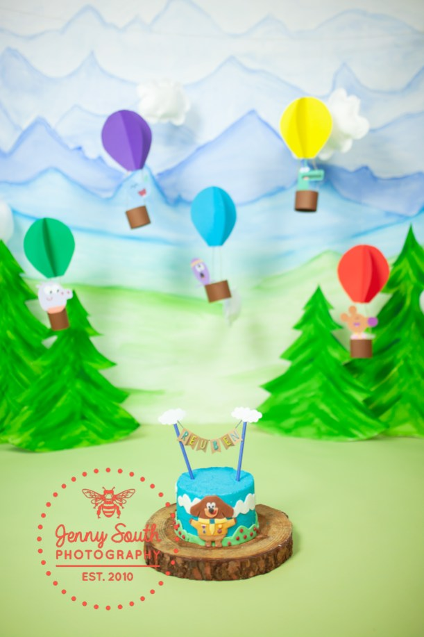 A hey Duggee cake with matching cake smash theme of hot air balloons and mountains.