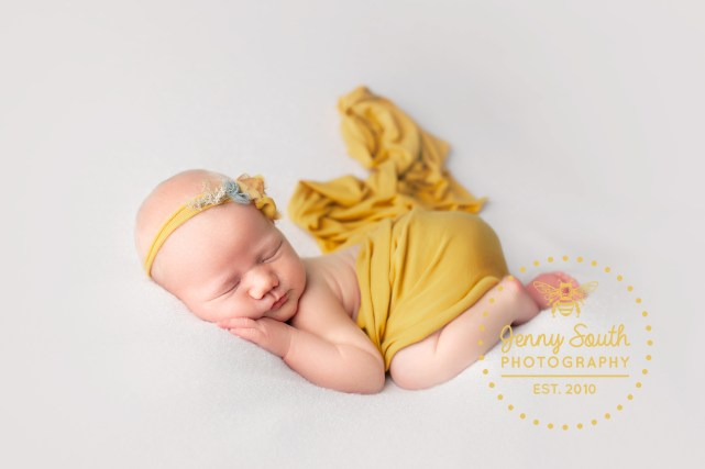 A baby girl sleeps on her belly wrapped in mustard accessories during a newborn photo shoot