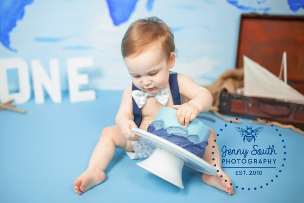 A baby boy grabs and smashes his cake during his first birthday cake smash.