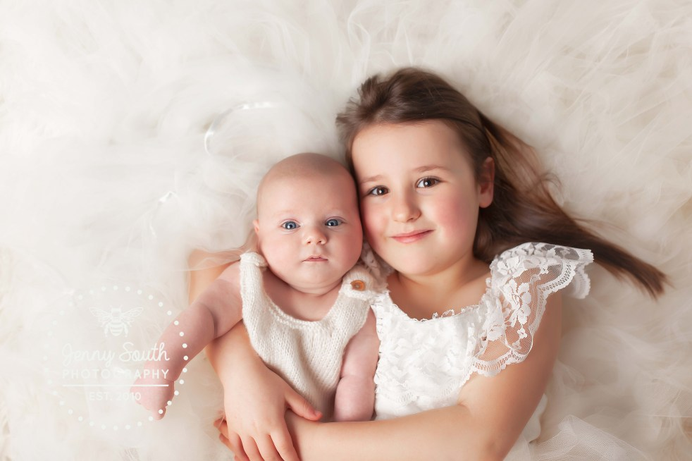 A proud big sister cuddles her baby brother during a family photo shoot in Plymouth