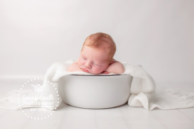 A newborn sleeps on his hands in a vintage white enamelled bowl, against a white backdrop.