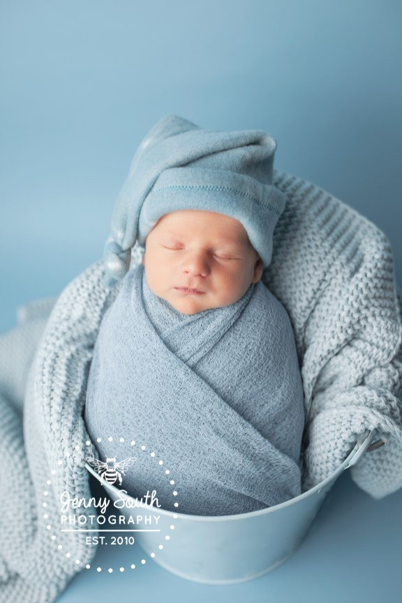 A newborn baby boy just a week old sleeps with a night cap on whilst he naps in a place blue bucket