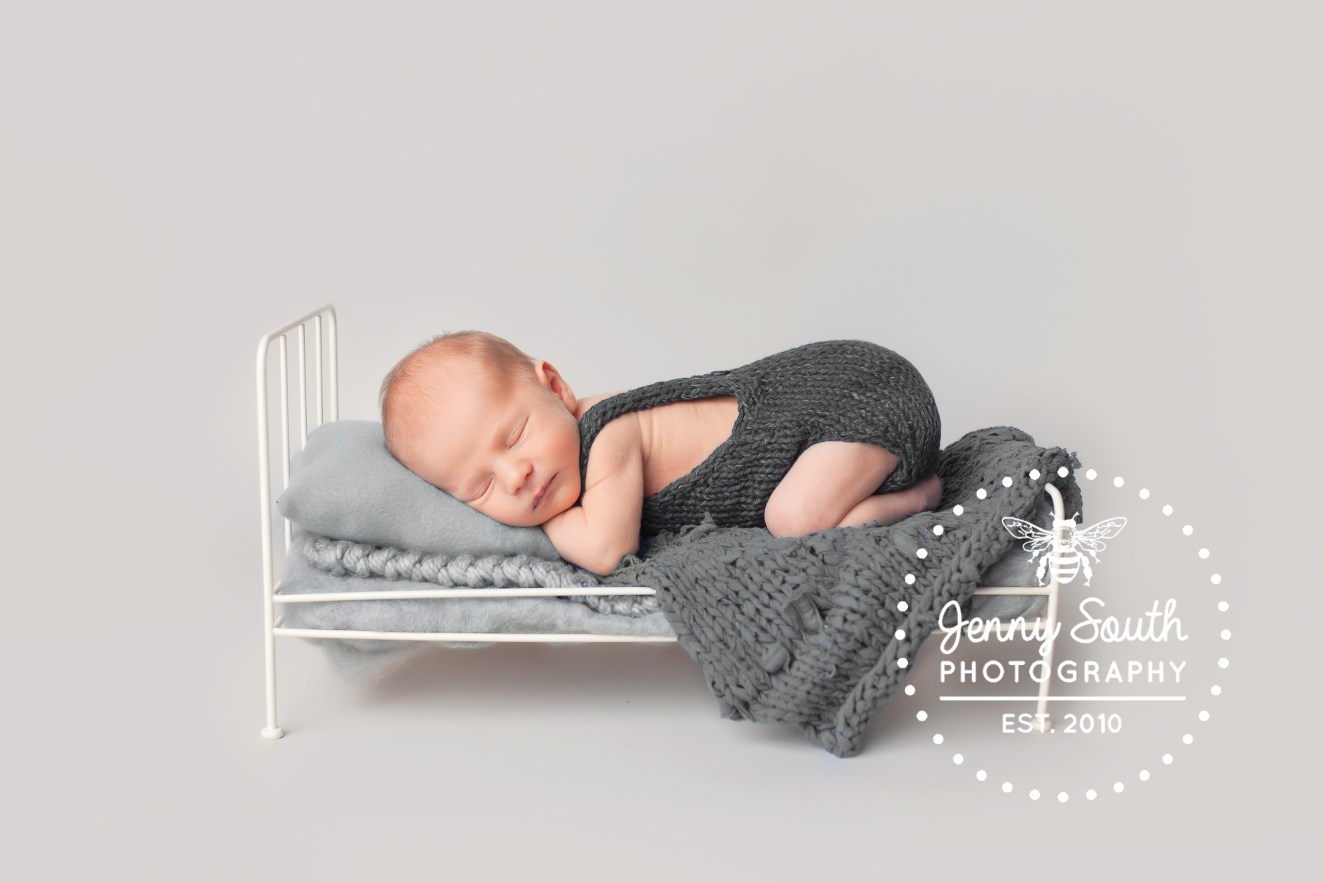 A one week old baby sleeps on his stomach on a miniature bed custom made for him. the whole image is shades of grey.