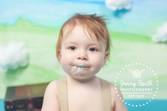 A little boy smiles sweetly covered in icing from his cake smash cake.