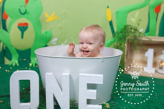 A baby boy who's just turned one splashes happily in a white tin bathtub at the end of his frog themed birthday cake smash.