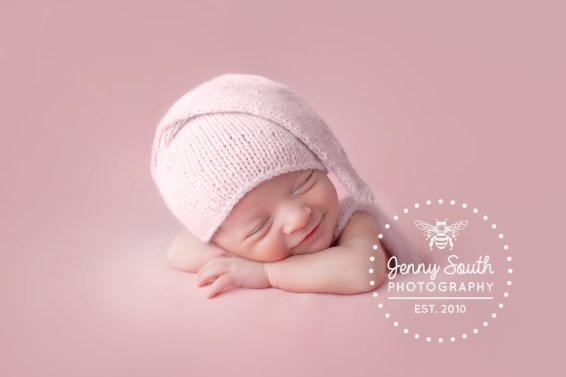 A beautiful baby girl smiles sweetly in her sleep on a pink background