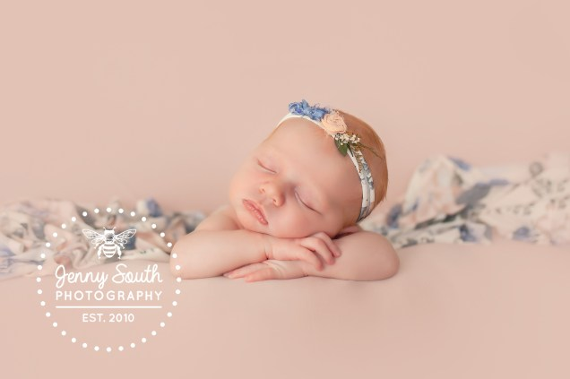 A baby girl sleeps on her hands against a blush pink backdrop wearing a floral headband for her first ever photo shoot in Plymouth.
