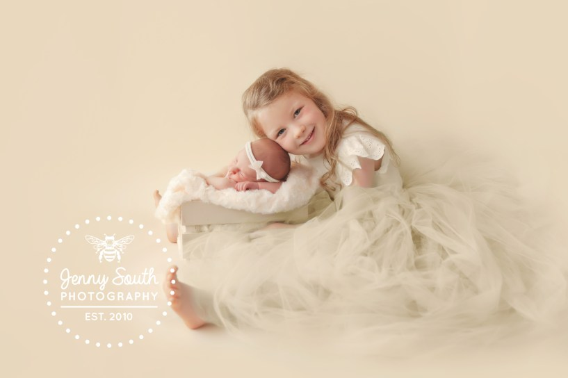 A proud big sister shows off her newborn sister during a family photo shoot in Plymouth