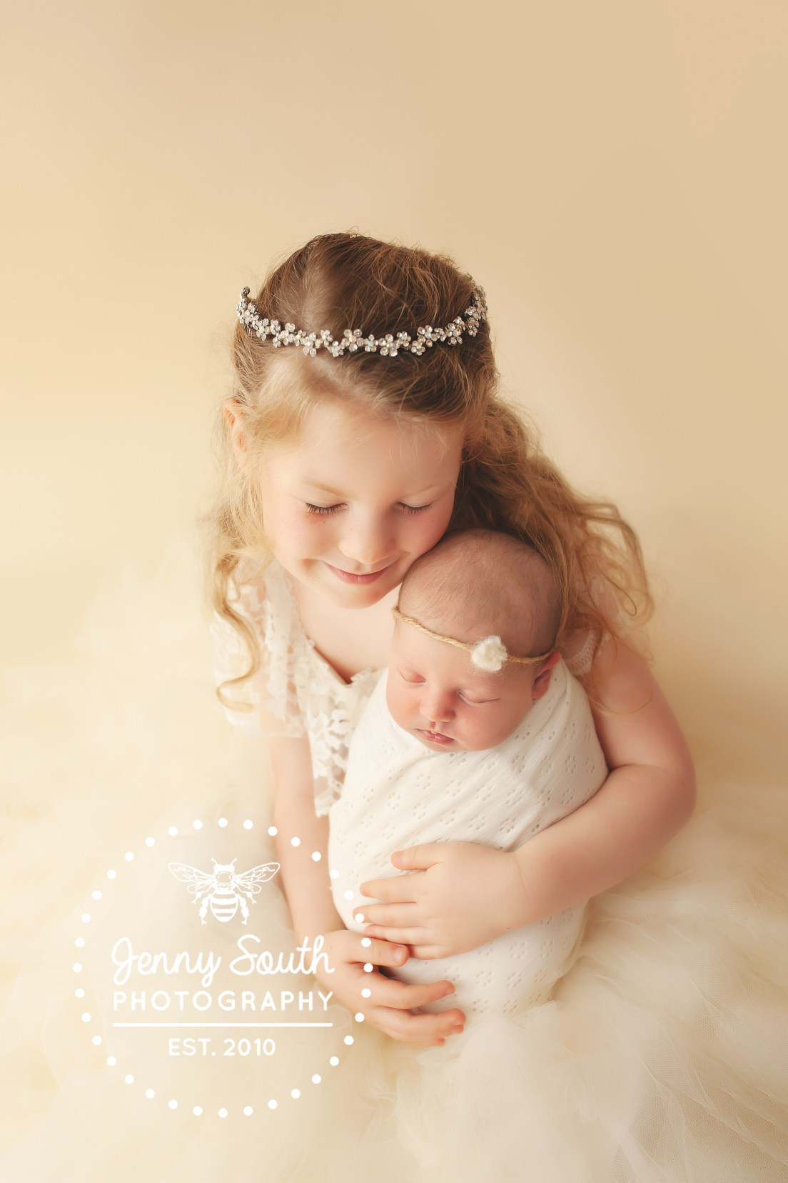 A heavenly image of two new sisters sharing a sweet embrace as they pose during a newborn photo shoot