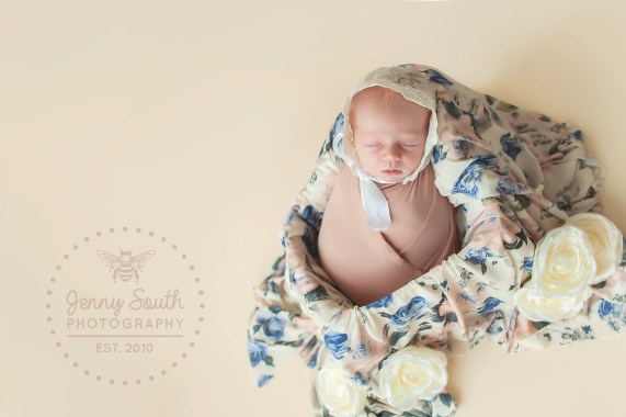 A tiny newborn baby girl sleeps soundly in a patterned floral create during her newborn session.