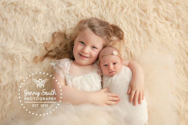 A big sister cuddles her little sister lovingly as they pose for a photograph together.
