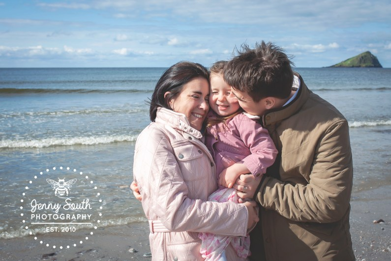 A mother and father snuggle into their only child during a family photo shoot on a beach near Plymouth