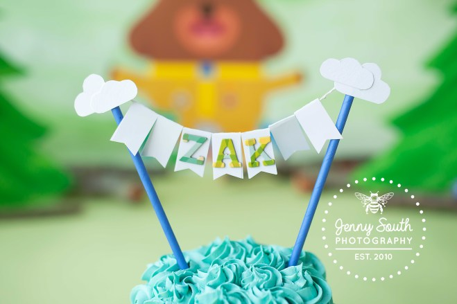A cake topper stands above a buttercream cake spelling out the name Zak