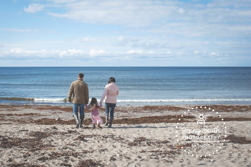 A family of 3 stare into the ocean on the people beach of Wembury located on the South Devon coast