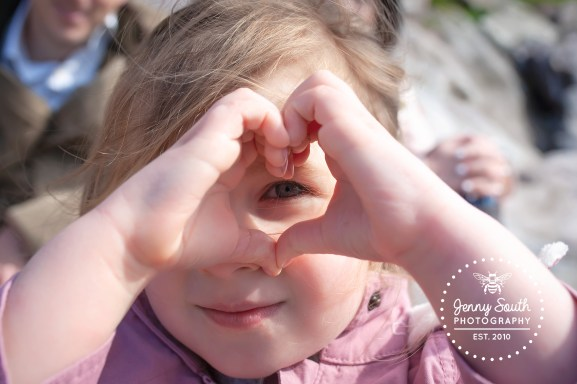 A little girl makes a love heart shape with her fingers and peeks through the middle