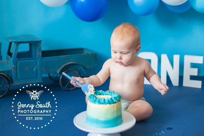 A little boy sit and eats his birthday cake with a wooden spoon.