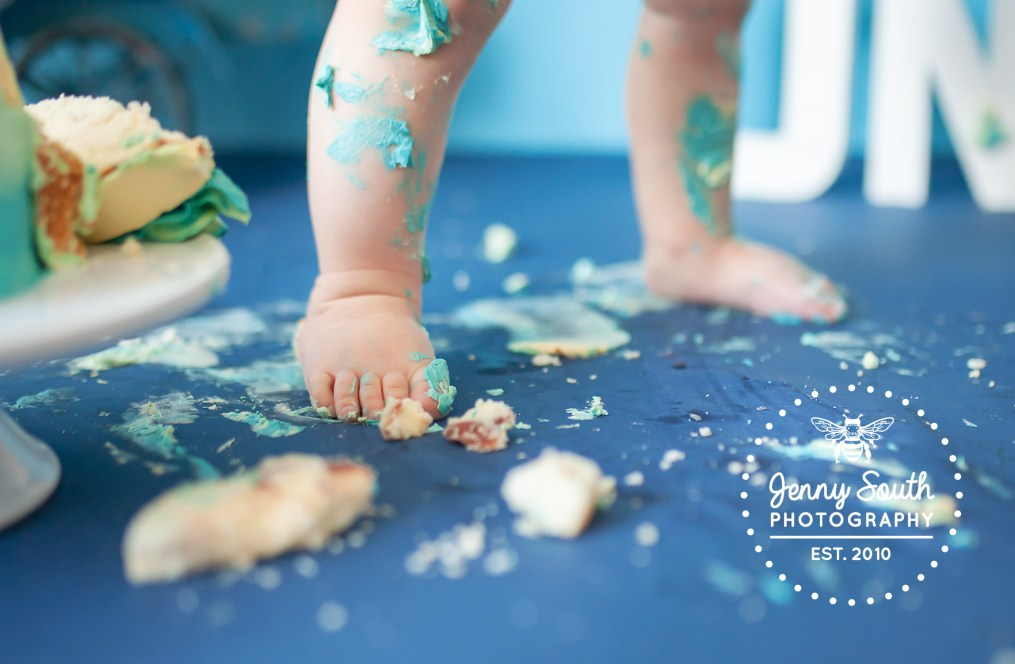 A messy scene and the tiny toes of a little boy covered in birthday cake