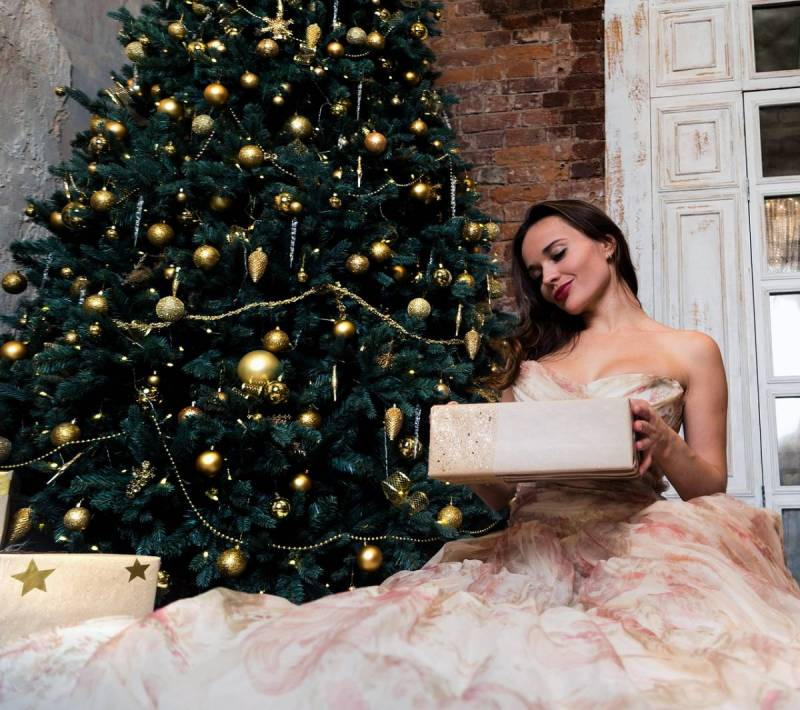 Woman with gown sitting next to Christmas tree