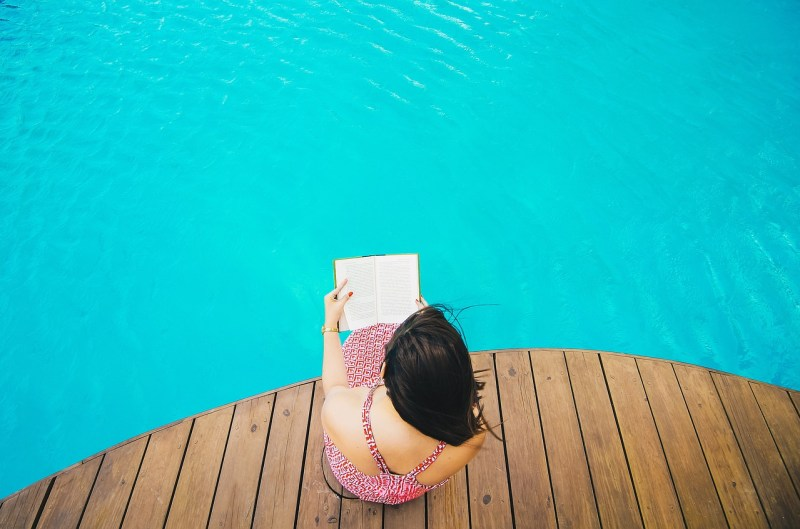 Woman reading by the pool
