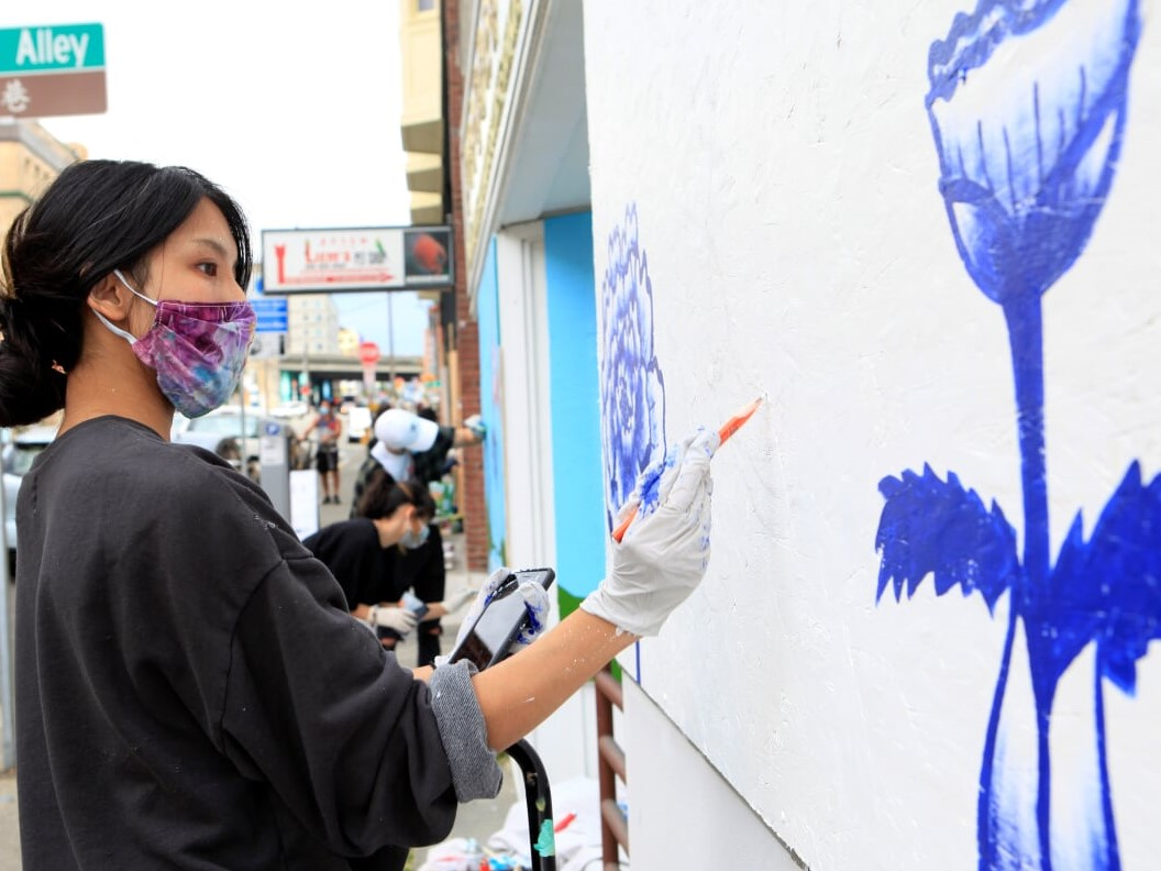 A woman in a mask paints blue florals on a  large canvas.P