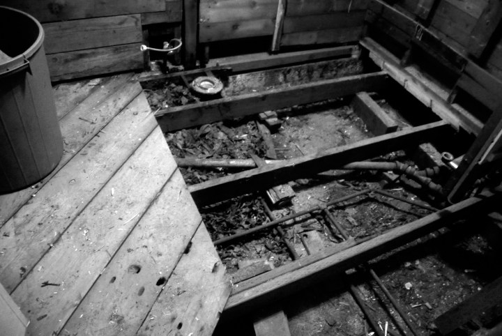 black and white image of a bathroom gutted down to the studs in order to remove hidden dry rot and create a structurally sound room.